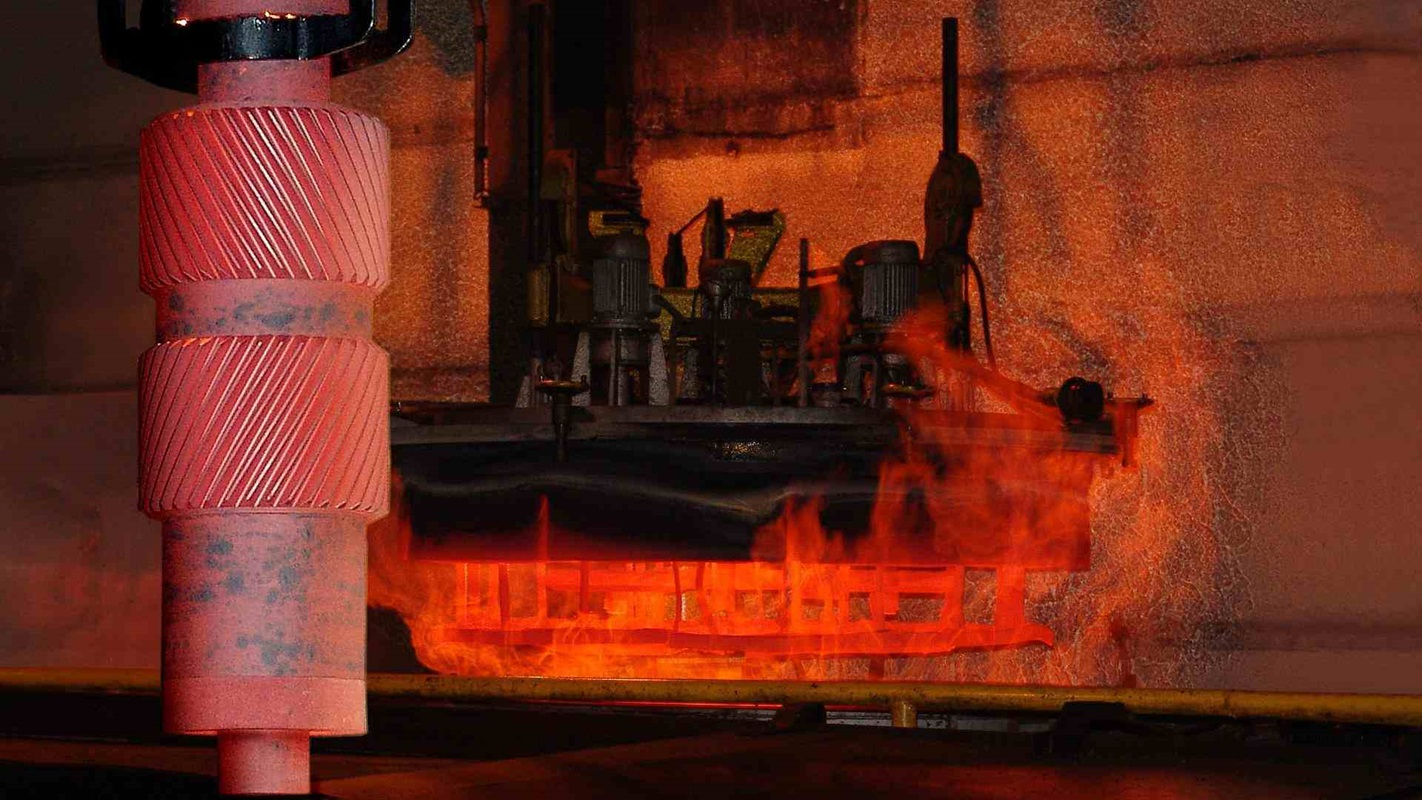 Red-hot SYMETRO intermediate pinion hanging in front of hardening furnace