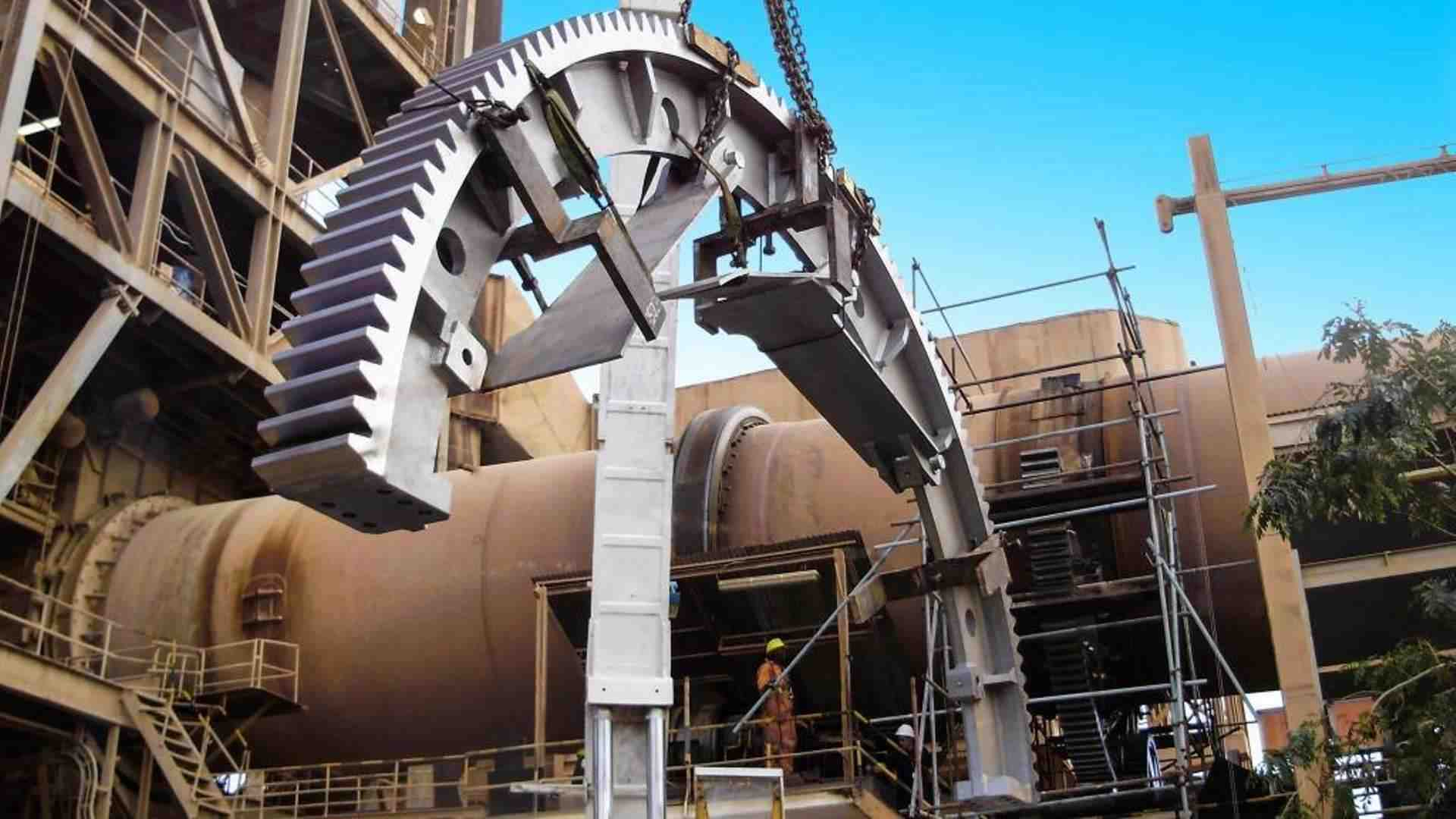MAAG® Girth gear hanging from a crane hook in front of a cement kiln