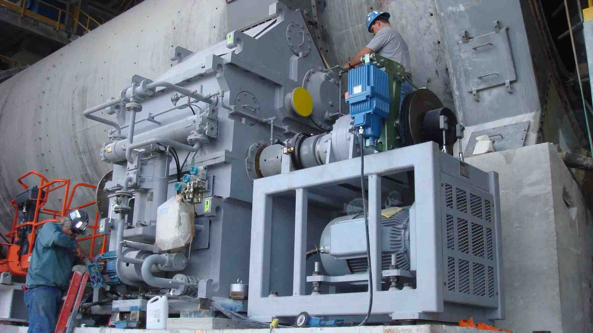 Two service engineers installing a lateral gear unit beside the cement mill